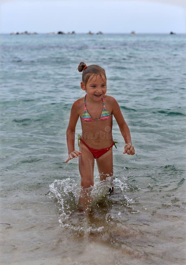 Ein lachendes kleines Mädchen, das in den Meereswellen steht stockfoto