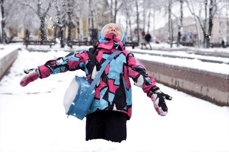 Ein lachendes kleines Mädchen, das mit Schnee spielt stockfotografie