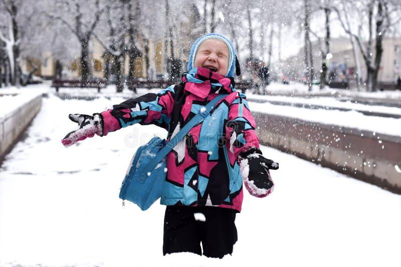 Ein lachendes kleines Mädchen, das mit Schnee spielt lizenzfreie stockfotos