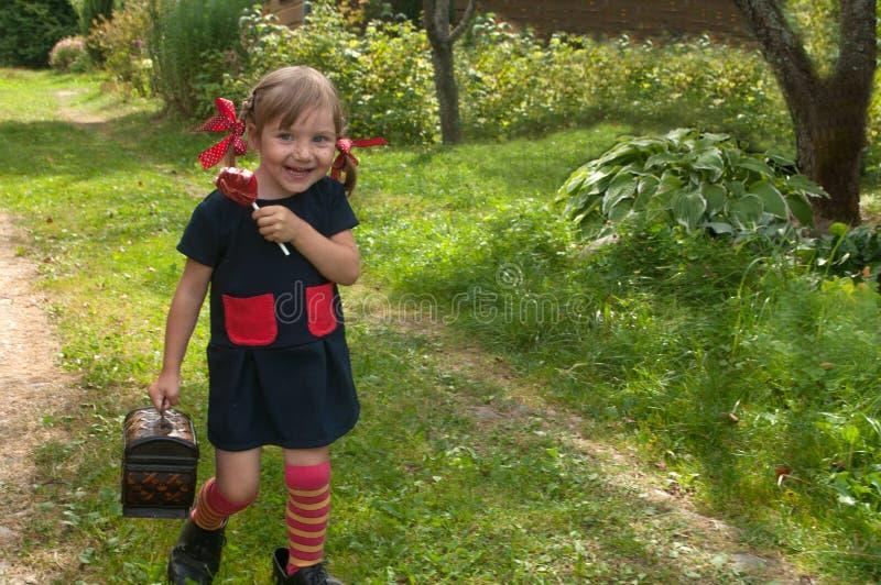 Ein lachendes kleines Mädchen, das Pippi Longstocking darstellt, auf einem Gartengras sitzt und einen Lutscher isst lizenzfreie stockfotos