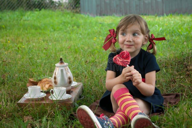 Ein lachendes kleines Mädchen, das Pippi Longstocking darstellt, auf einem Gartengras sitzt und einen Lutscher isst stockbild