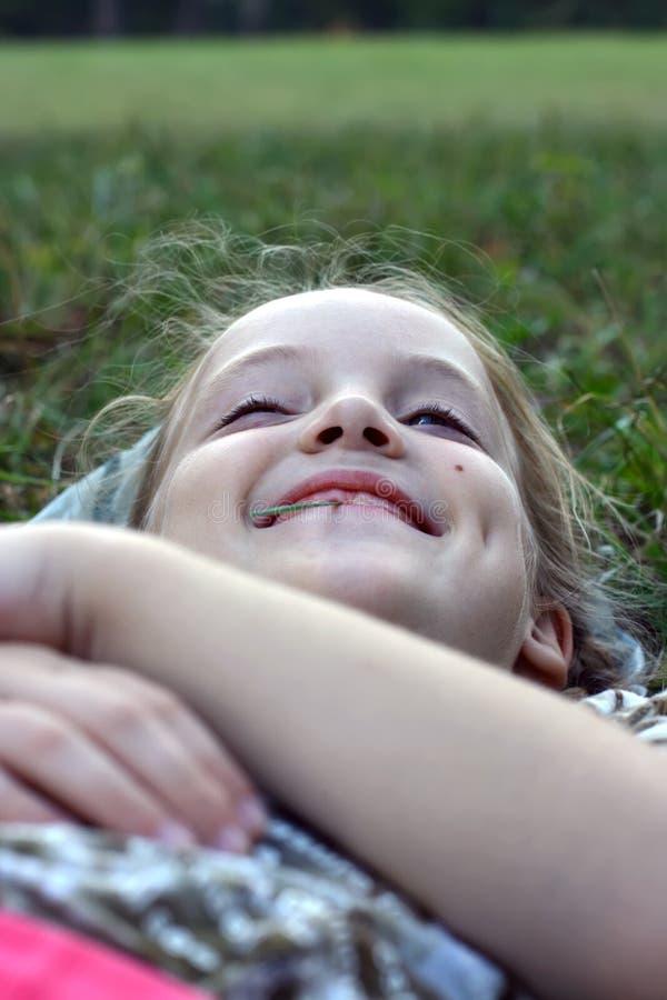 Ein lachendes kleines Mädchen liegt auf dem Gras mit einem Grashalm in ihrem Mund stockfotos