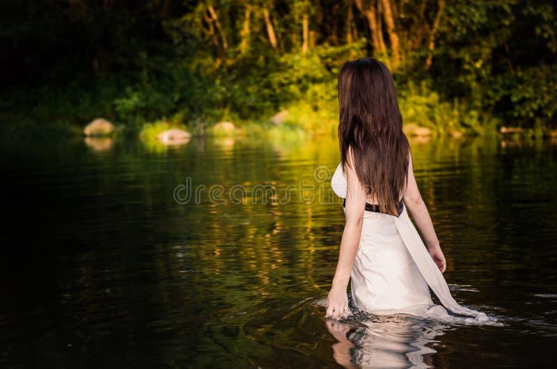 Ein langhaariges Sitzmädchen mit weißem Kleid gehend durch das rührende Wasser des Flusses stockbild