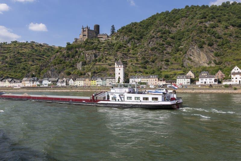 Ein Lastkahn mit Frachtsegeln entlang dem Rhein gegen den Hintergrund des Dorfs und des alten Schlosses stockbild