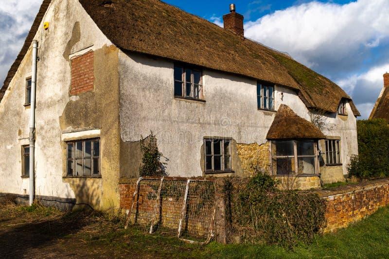 Ein Lauf hinunter englisches Bauernhaus mit einem Strohdach lizenzfreies stockfoto