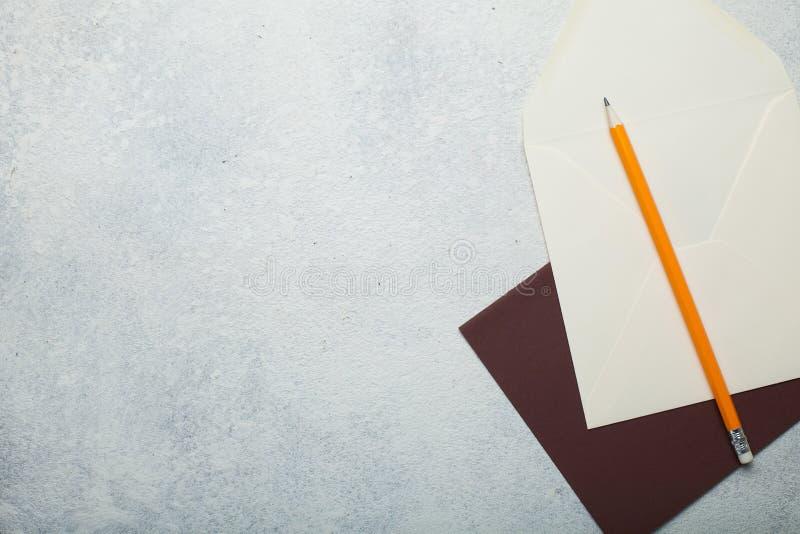 Ein leeres Blatt Papier und ein Umschlag mit einem gelben Bleistift Leerer Raum auf weißer Weinleseform lizenzfreie stockfotos