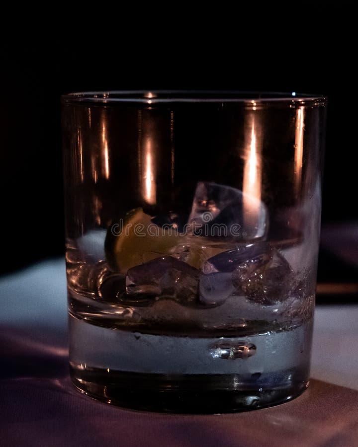 Ein leeres Glas Gin Tonic-Stände auf einer schwach beleuchteten weißen Tischdecke lizenzfreie stockfotos