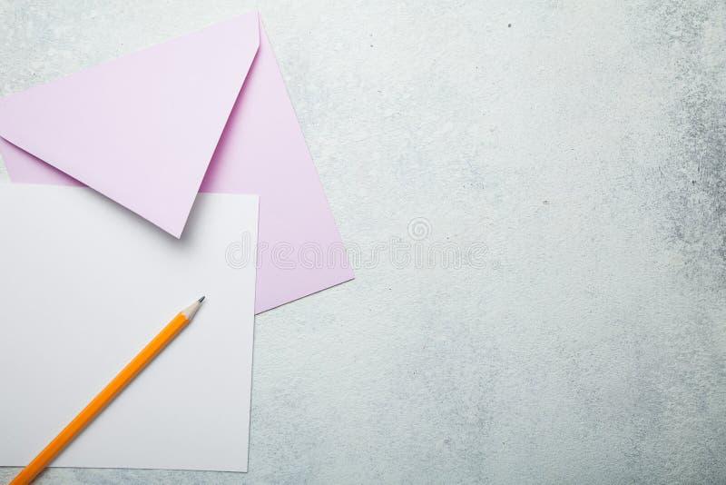 Ein leeres quadratisches Blatt Papier mit einem rosa Umschlag auf einem weißen Weinlesehintergrund, ein Liebesbrief zum Valentins stockbilder