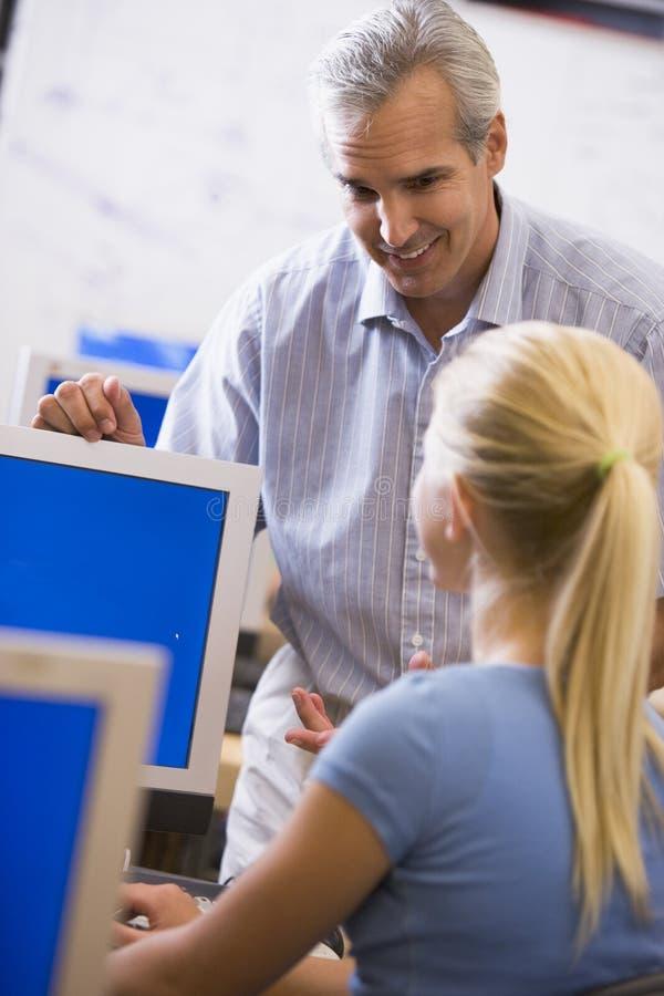 Ein Lehrer spricht mit einem Schulmädchen, das einen Computer verwendet stockbild