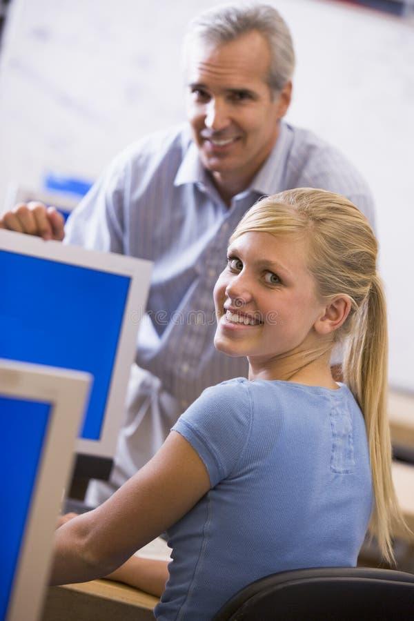 Ein Lehrer spricht mit einem Schulmädchen, das einen Computer verwendet stockbilder
