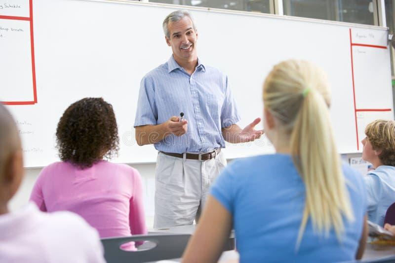 Ein Lehrer spricht mit Schulkindern in einer Kategorie stockfoto