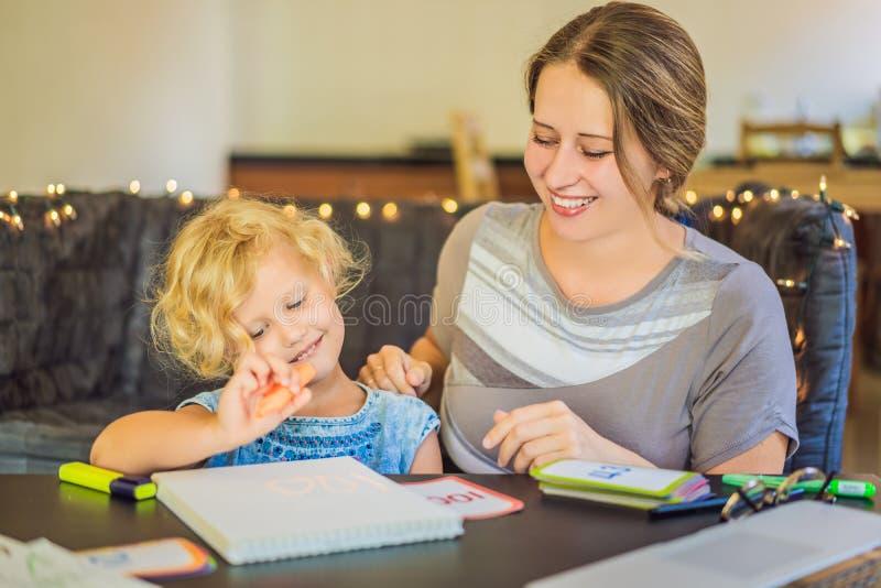 Ein Lehrer, ein Tutor für Hausunterricht und ein Lehrer am Tisch Oder Mutter und Tochter homeschooling stockbilder