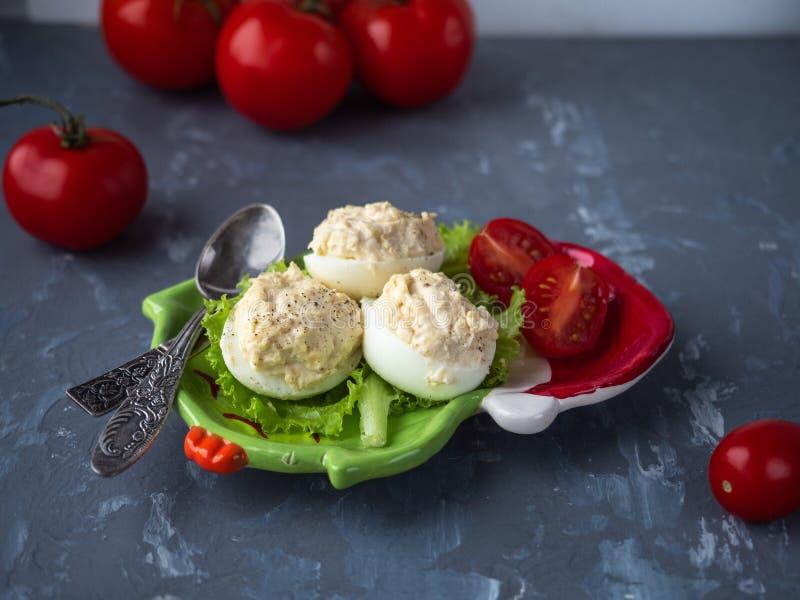 Ein leichtes Mittagessen mit gefüllten Eiern, Kirschtomaten und Salat auf einem Teller mit Cutlery Rote Tomaten stockbilder