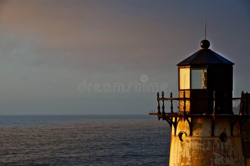 Ein Leuchtturm starrt weg in Richtung zum Sonnenuntergang an stockbilder