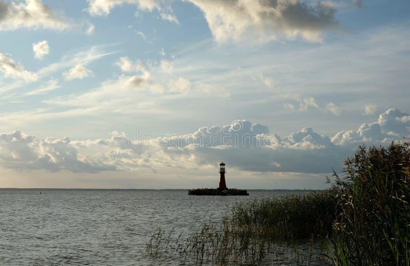 Ein Leuchtturm und weißen flaumigen Wolken lizenzfreies stockbild