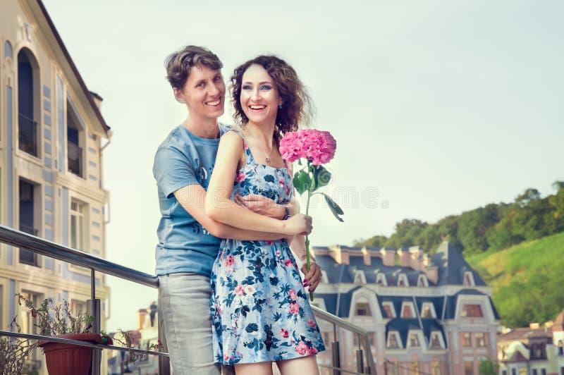 Ein liebevolles Paar ist, lachend glücklich umfassend und vor dem hintergrund einer alten Straße und eines klaren Himmels Das Mäd lizenzfreies stockfoto