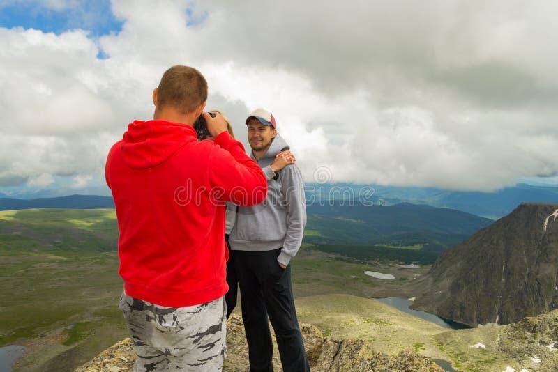 Ein liebevolles Paar steht auf dem Berg, der vor küsst lizenzfreies stockbild