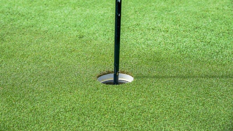 Ein Loch des Golfballs im Golfplatz stockbilder