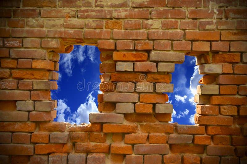 Ein Loch in einer Backsteinmauer, die den Himmel übersieht stockfotografie