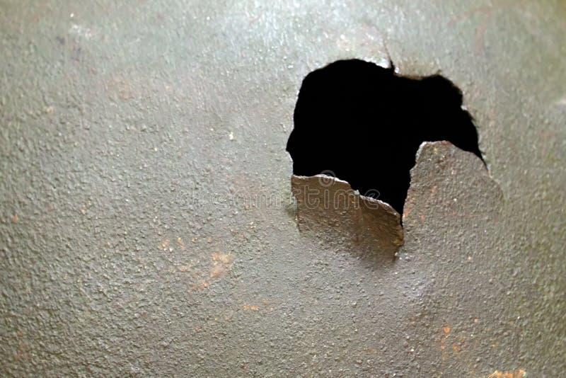 Ein Loch mit heftigen Rändern in einer dunkelgrünen Stahloberfläche Nahaufnahme, flache Schärfentiefe lizenzfreies stockfoto