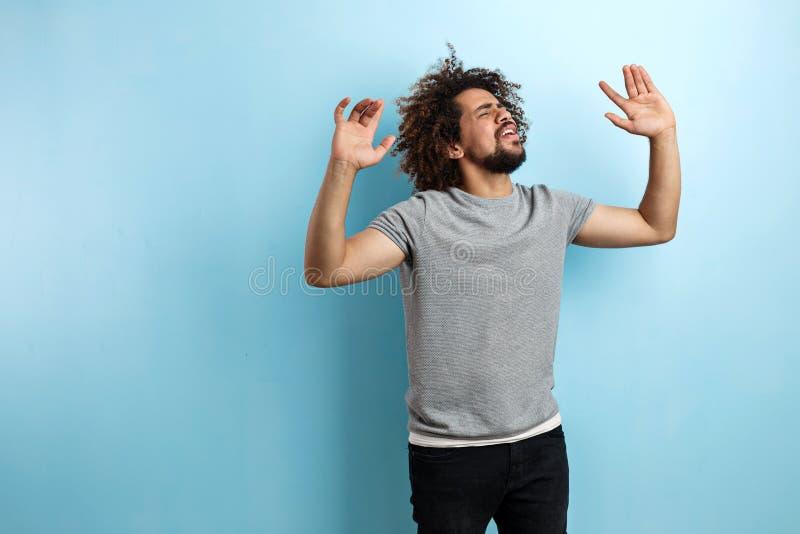 Ein lockiger gut aussehender Mann, der ein graues T-Shirt trägt, steht mit einem erfüllten Ausdruck auf dem Gesicht und tanzt mit stockfotografie