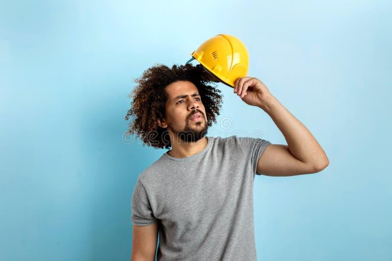 Ein lockiger gut aussehender Mann, der ein graues T-Shirt trägt, steht mit einem Schutzhelm, der seitlich mit konzentriert schaut lizenzfreie stockfotografie