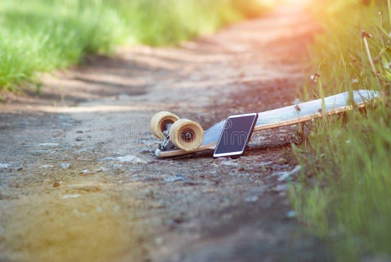 Ein longboard und ein Smartphone Popularisierung der Skateboardbewegung im Social Media, Nebenkultur, lizenzfreie stockfotografie