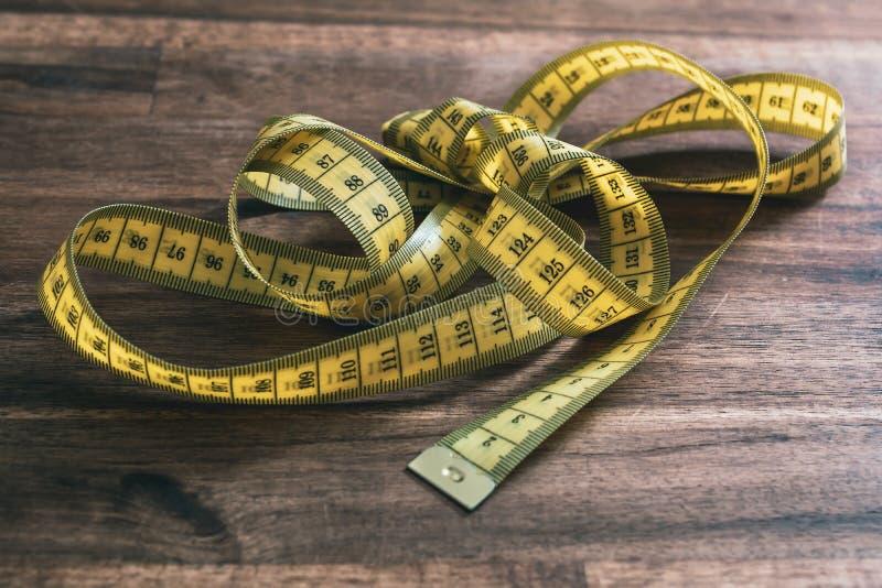Ein loses verwirrtes oben gelbes messendes Band auf einem alten Holztisch stockfotos