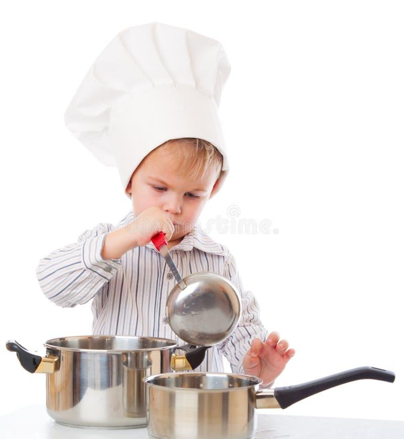 Ein lustiger Junge schildert einen Koch lizenzfreies stockbild