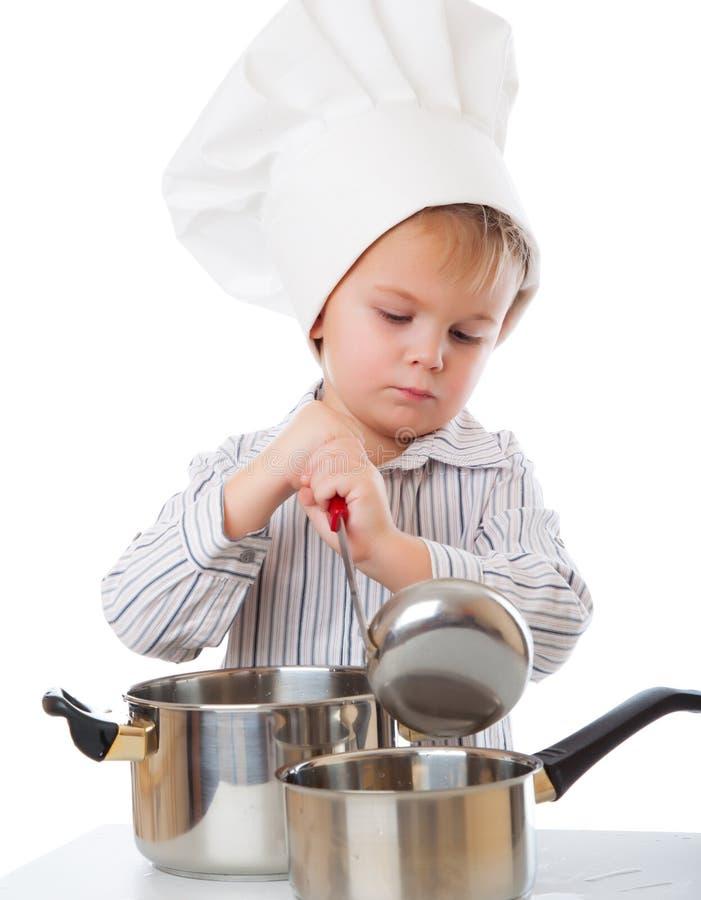 Ein lustiger Junge schildert einen Koch stockfotografie