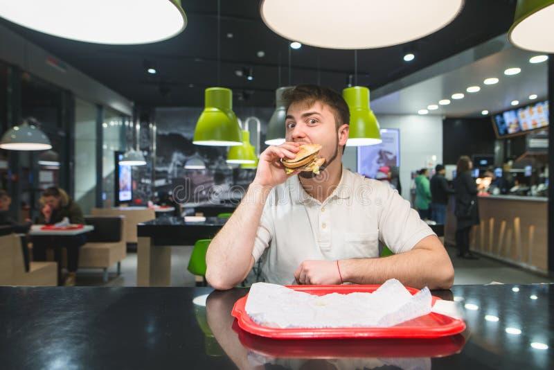 Ein lustiger Mann isst einen appetitanregenden Burger in einem Restaurant und betrachtet die Kamera Schnellimbissmittagessen stockfoto