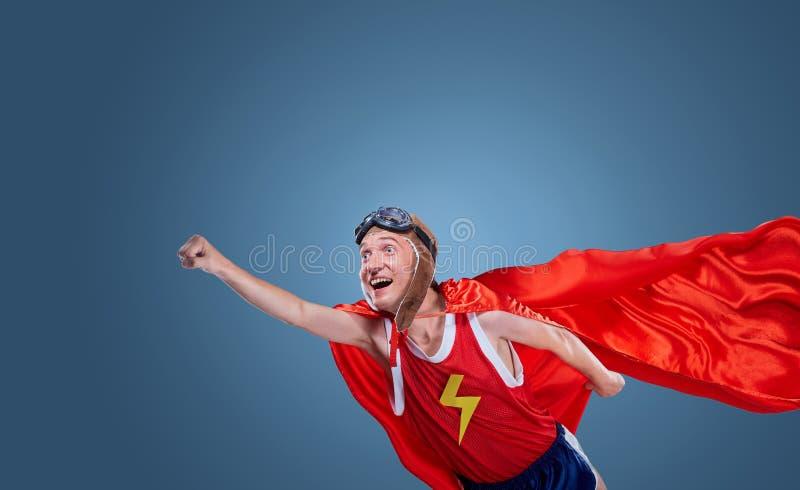 Ein lustiger Superheld fliegt stockbilder