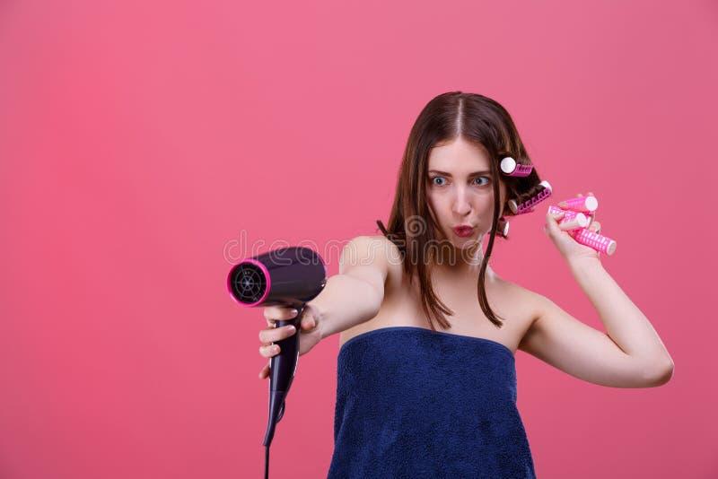 Ein lustiges Mädchen, in einem blauen Badtuch, mit Haarlockenwicklern, hält einen Haartrockner vor ihrem und verzieht ihr Gesicht stockbild