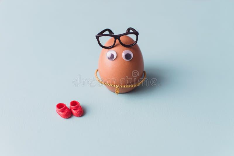Ein lustiges nettes braunes Ei mit schwarzen Gl?sern und roten Schuhen auf blauem Hintergrund stockbild
