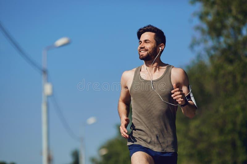 Ein männlicher Läufer läuft entlang die Straße zum Park lizenzfreie stockfotos