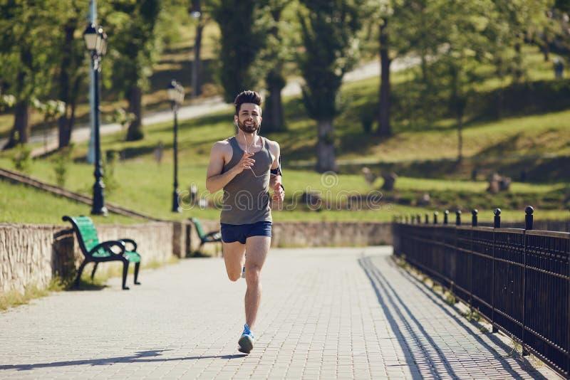 Ein männlicher Läufer läuft entlang die Straße zum Park lizenzfreies stockbild