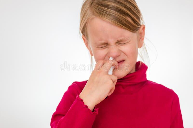 Ein Mädchen überwindt seine Furcht und benutzt Nasenspray stockfotografie