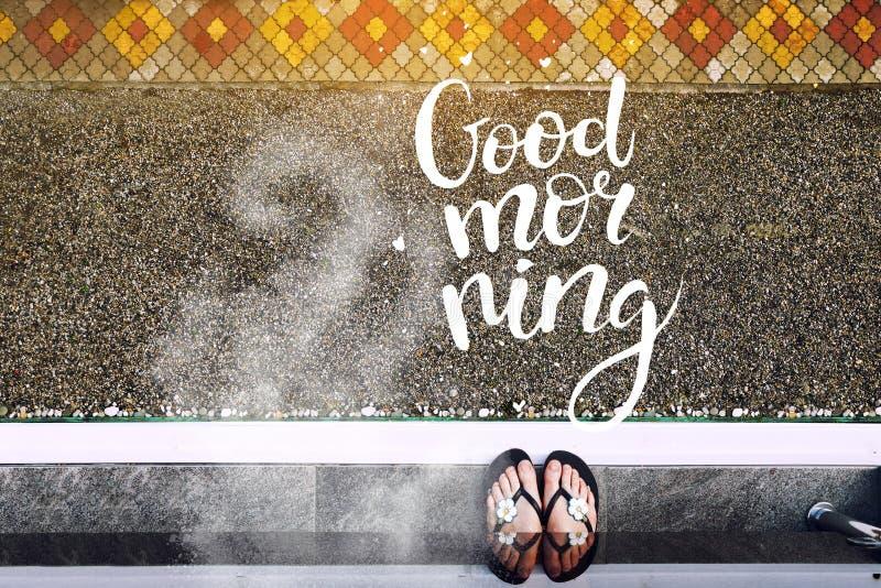 Ein Mädchen auf dem Balkon am frühen Morgen Wolke des Kaffeearomas und der Aufschrift des guten Morgens stockfoto