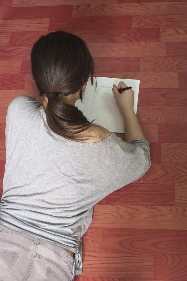 Ein Mädchen, das auf dem Boden tut ihre Hausarbeit liegt stockfotografie