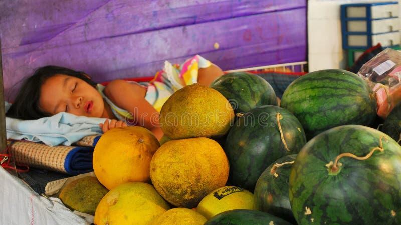 Ein Mädchen, das auf einem Markt schläft thailand lizenzfreies stockfoto