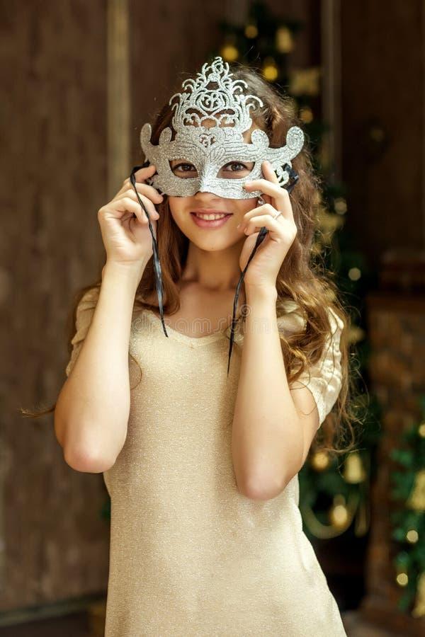Ein Mädchen, das auf einer Maskerademaske während der Weihnachts- und des neuen Jahresfeiern versucht lizenzfreies stockbild