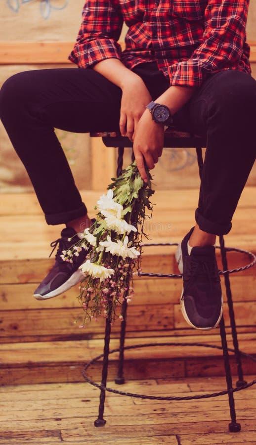 Ein Mädchen, das ein Blume boquet auf dem Stuhl in einer Kaffeestube hält stockbilder