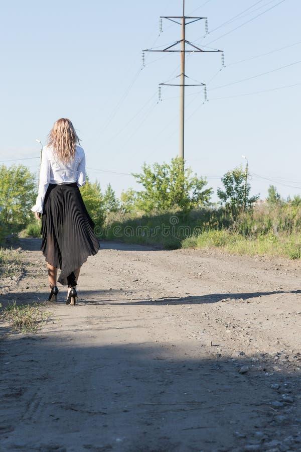 Ein Mädchen, das entlang die Straße geht lizenzfreies stockfoto
