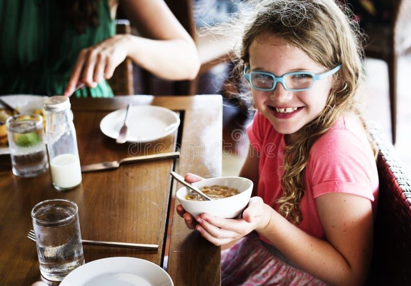 Ein Mädchen, das ihre Müslischüssel zum Frühstück hält stockbilder