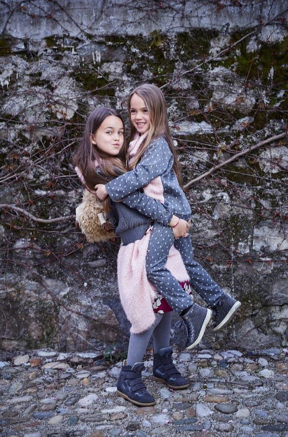 Ein Mädchen, das ihre Schwester in den Armen hält stockfoto