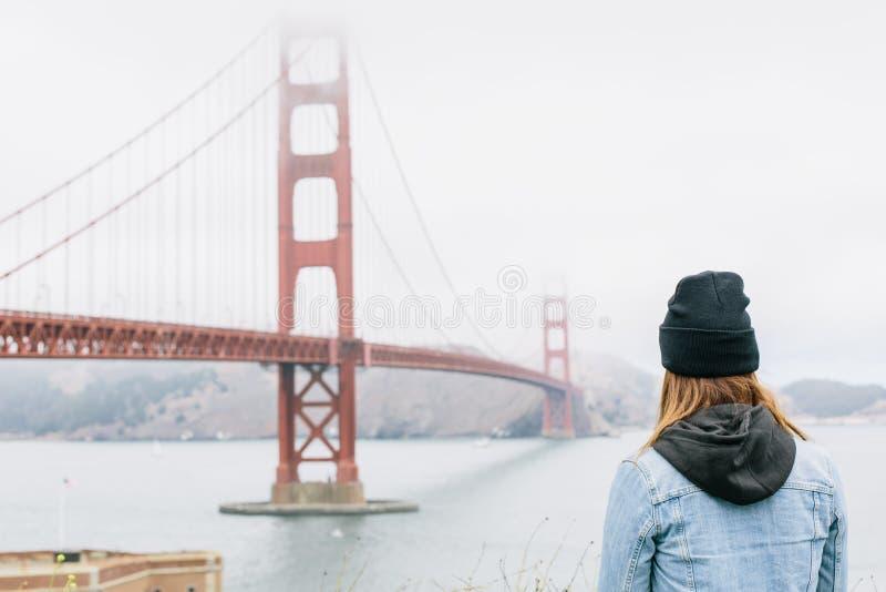 Ein Mädchen, das in Richtung Golden gate bridges in San Francisco, Kalifornien blickt stockfotos