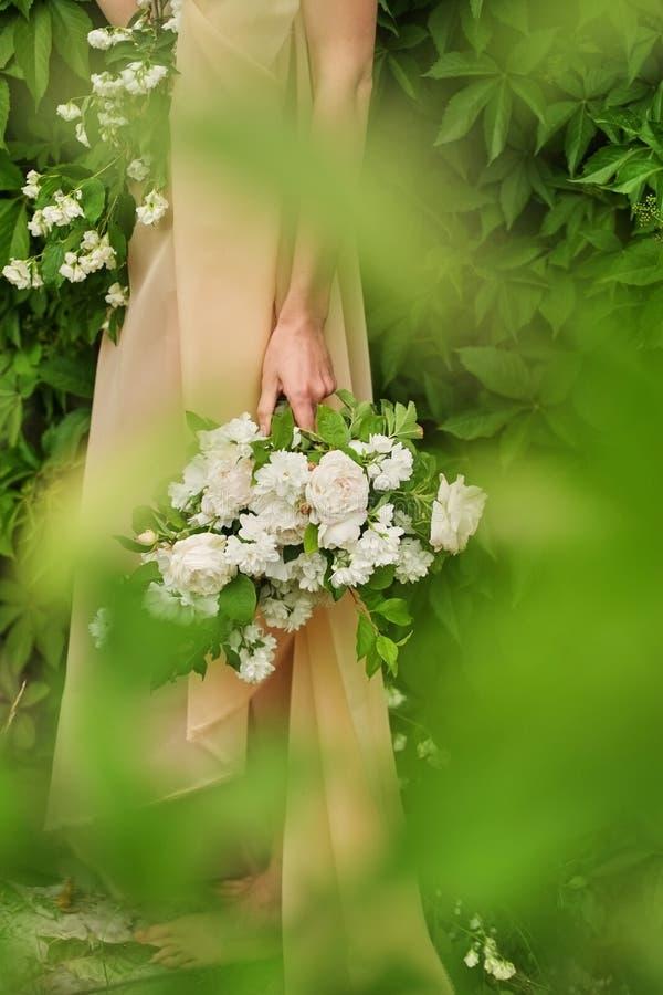 Ein Mädchen, das ein romantisches rosa Kleid hält einen Blumenstrauß von weißen Rosen, draußen stehend, leichtes Cu Pastellfarben stockfotografie