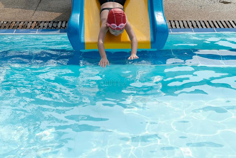 ein Mädchen, das Schieber in swimmimg Pool spielt stockfotos
