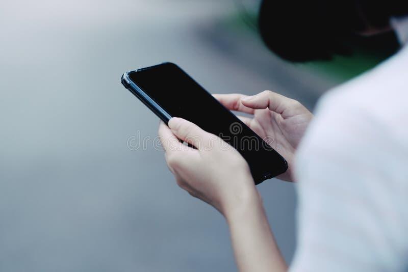 Ein Mädchen, das schwarzen Smartphone für das on-line-Einkaufen verwendet stockfotografie