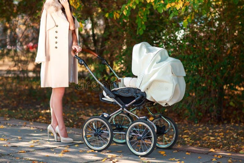 Ein Mädchen in den Fersen und mit einem Spaziergänger steht im Park stockbilder